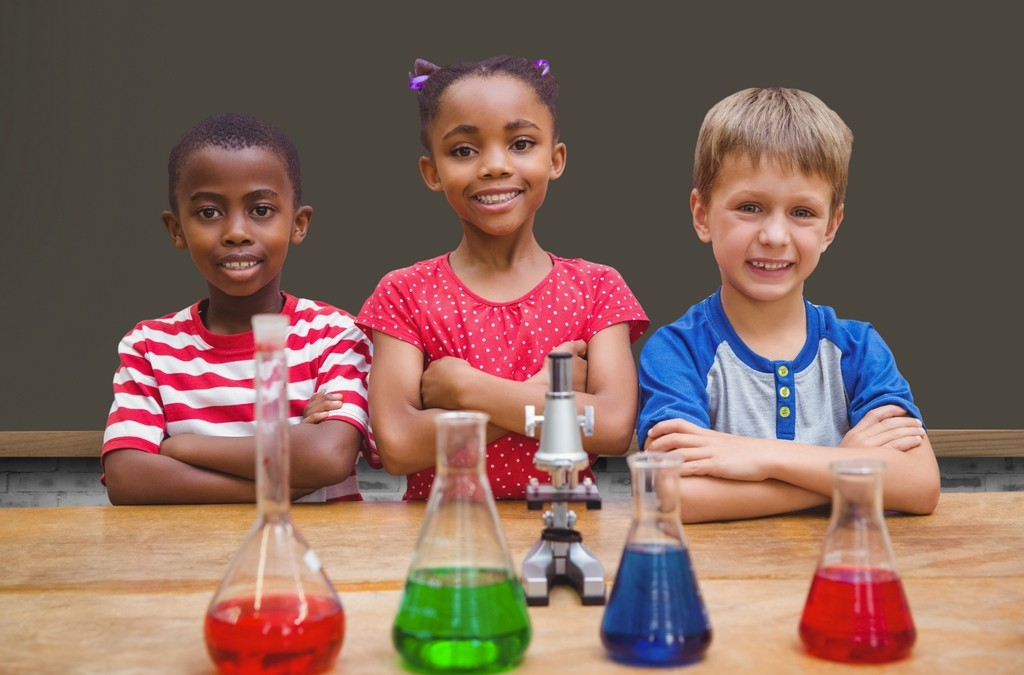 Portrait of children standing with arms crossed in chemistry lab