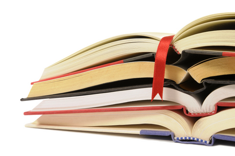 Small pile of open books with red bookmark ribbon isolated on white background
