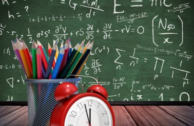 Digital composition of alarm clock with colorful pencils on wooden board against formula background