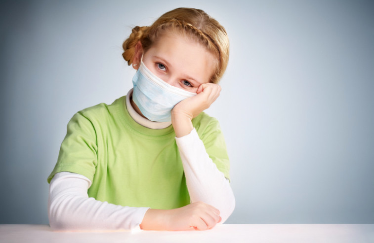 A little girl sitting in protective mask